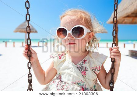 Little girl swinging with tropical beach on background