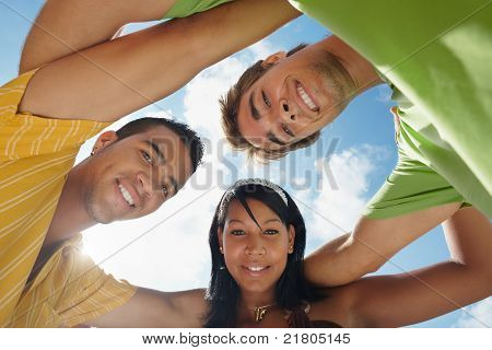 Team Of Men And Woman Embracing And Smiling At Camera