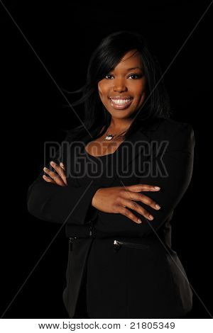 Portrait of young African American businesswoman smiling with arms crossed isolated over black background