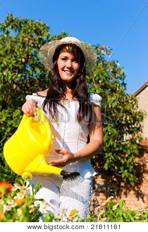 Gardening in summer - woman watering flowers with a yellow watering can; she is wearing a hat