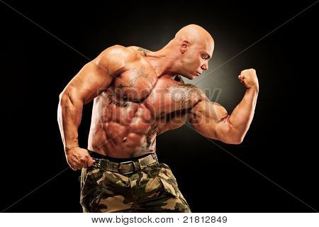 A bodybuilder showing his muscles isolated on black background