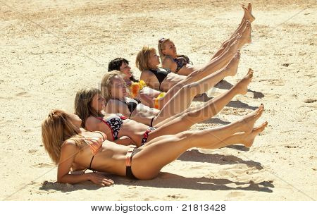 Photo of several girls in bikini lying on sandy beach and tanning in the bright summer sun