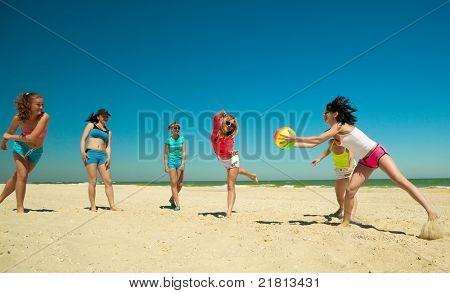 Gruppe junger fröhliche Mädchen spielen Volleyball, übergeben den Ball an einander am Strand