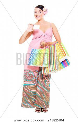 full-length portrait of smiley young woman with credit card and shopping bags. isolated on white background