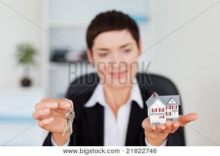 Smiling Woman Showing A Miniature House And A Key