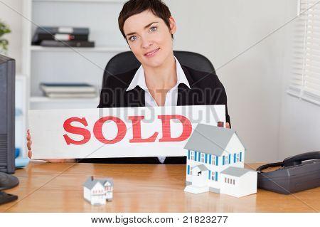 Weibliche Immobilienmakler mit A verkauft Panel und Häuser Miniatures