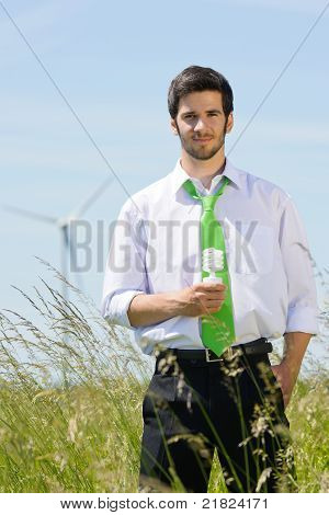 Green Energy Businessman In Field Hold Bulb