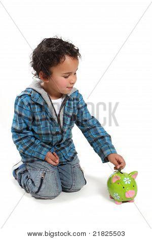Little Boy Putting Money Into A Piggy Bank