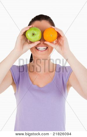 Portrait Of An Attractive Woman Playing With Fruits While Standing