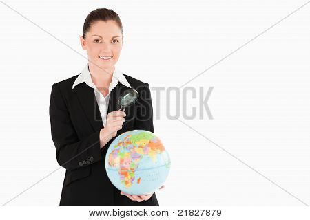 Pretty Female In Suit Holding A Globe And Using A Magnifying Glass