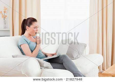 Surprised Woman Gambling With Her Computer While Sitting On A Sofa