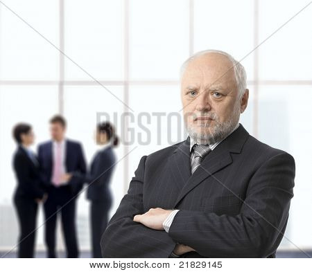 Portrait of serious senior businessman standing with arms folded in office lobby, colleagues in background.?