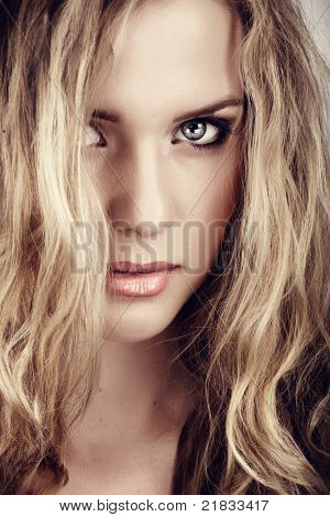 closeup portrait of young beautiful blonde woman with long curly hair and natural fresh make-up and summer tan