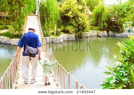 Young father holding hands with small toddler son as he teaches him to balance and walk on the bridge over lake in Park in Turkey