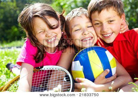 Drei Kinder mit Sportgeräten umarmen, Blick in die Kamera und lächelnd