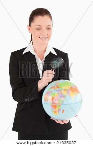 Beautiful female in suit holding a globe and using a magnifying glass while standing against a white background