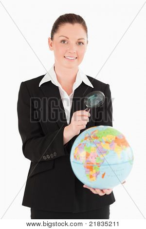 Charming female in suit holding a globe and using a magnifying glass while standing against a white background