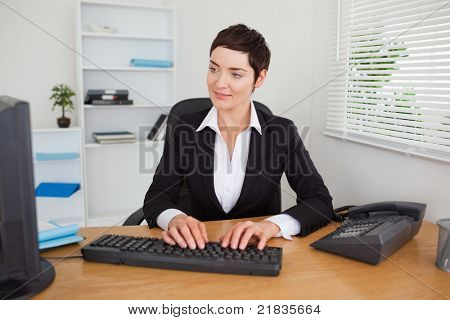 Charming secretary typing on her keyboard in her office