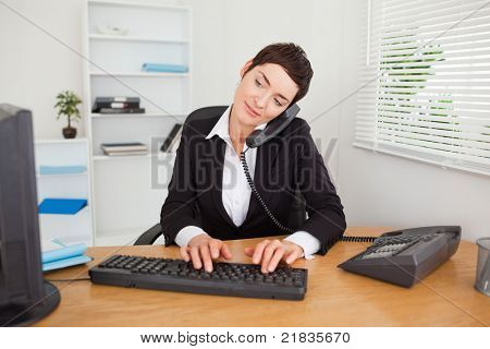 Active secretary answering the phone in her office