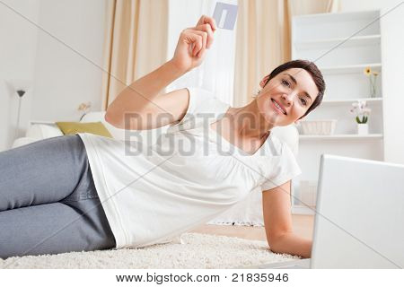Woman using her credit card to pay on line while looking at the camera