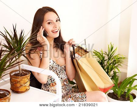 Woman in shop calling by phone.
