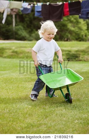 Cute young baby boy pushing a wheelbarrow in garden with clothes hanging in the background