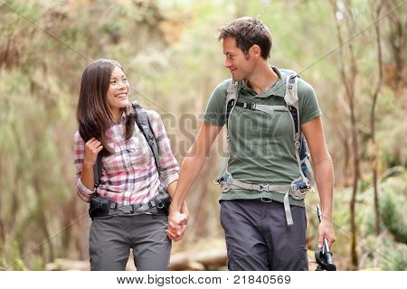 Young couple hiking in forest looking happy. Man and woman hikers holding hands walking in nature. From Aguamansa, Tenerife, Spain