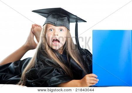 Cute little girl in graduation dress with blue book on isolated white