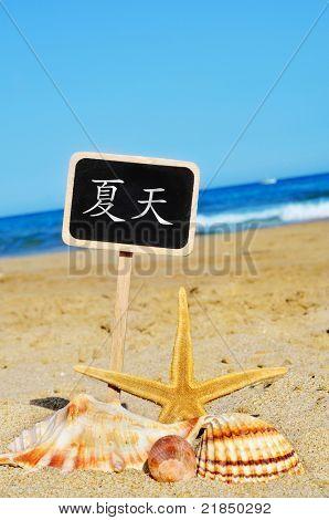 summer written in chinese in a blackboard on the beach