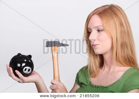 Young woman holding piggy bank and hammer