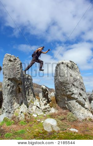 Young Man In Flee From One Rock To Another