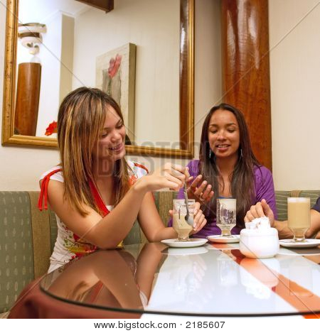 Two Mulatto Girls Drink Coffee In A Restaurant With Mirrors