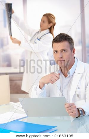 Male doctor sitting at desk, doing paperwork, female doctor in background looking at x-ray image.?