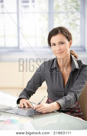 Attractive female graphic designer working on tablet, smiling.?