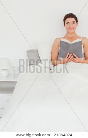 Portrait of a brunette holding a book while looking at the camera