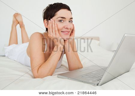 Charming woman using a laptop in her bedroom