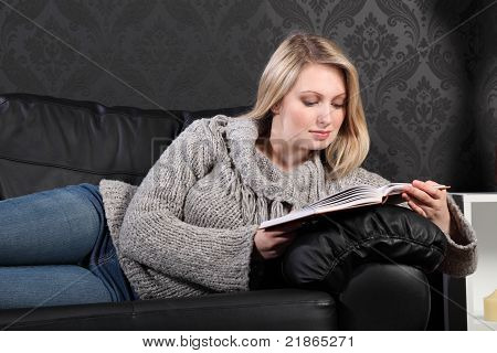 Beautiful Young Blonde Woman Reading Book At Home