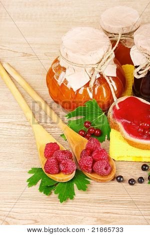 tasty fruit and berry jam on a wooden background