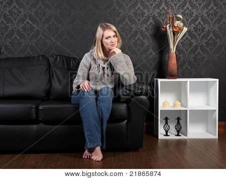 Casual Blonde Girl Home Relaxing On Leather Couch