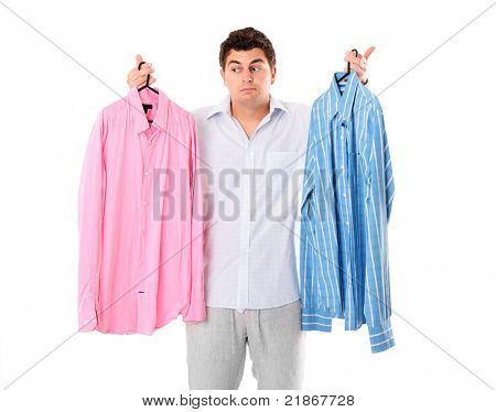 A portrait of an undecided man trying to choose between two shirts over white background