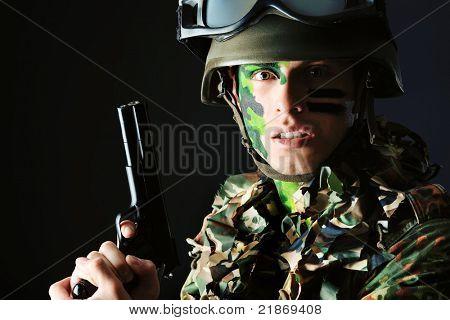 Disparo de un soldado conceptual pintado en colores caqui. Studio disparó sobre fondo negro.