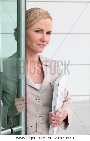 Blonde woman with a laptop in her arms