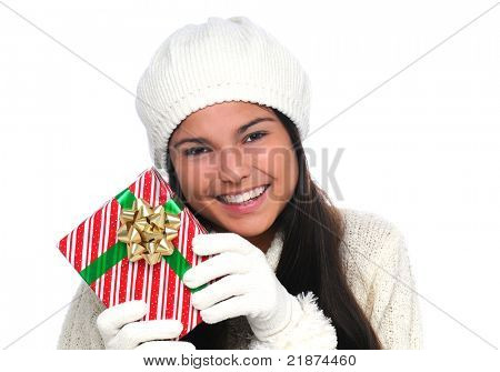Attractive smiling young woman holding a Christmas present near her face. Closeup in horizontal format over white.