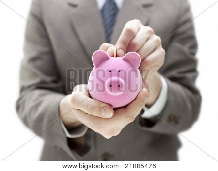 Businessman putting coin into the piggy bank