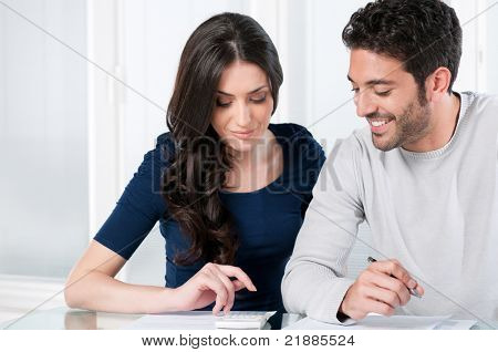Happy smiling couple calculating their financial investments at home