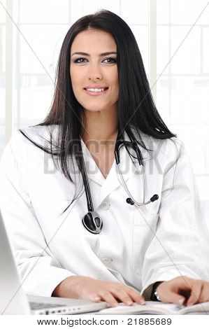 Young doctor woman looking to camera with smile, sitting on her desk