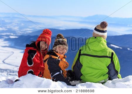 Three children playing in winter snow with mountains in the background.