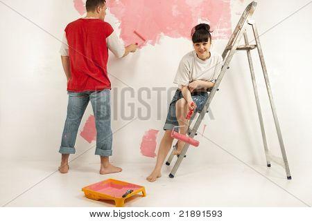 Fröhlich junges Paar von Arbeitnehmern, die Vorbereitung auf eine Wand malen