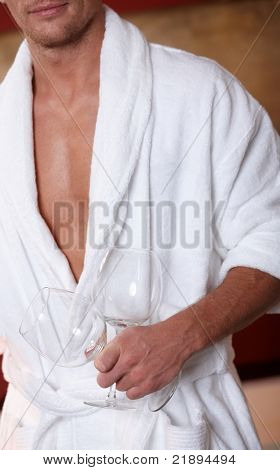 Sporty man in bathrobe holding wine glasses.?