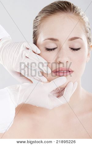 doctor checking woman's lips before cosmetic surgery